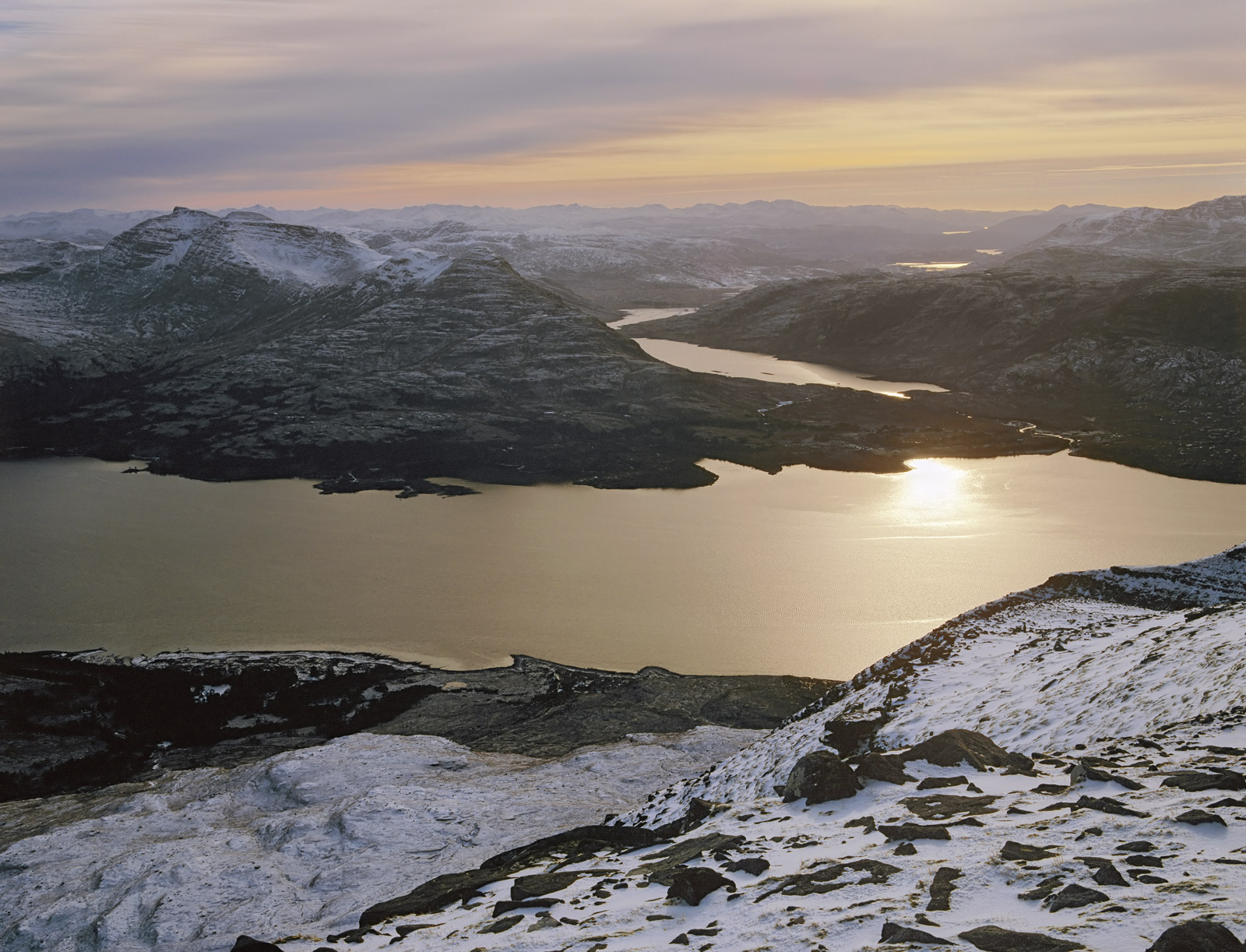 High on the top of a munro looking down at snow dusted Loch Torridon at sunset, up there you feel it is your own personal mountain...