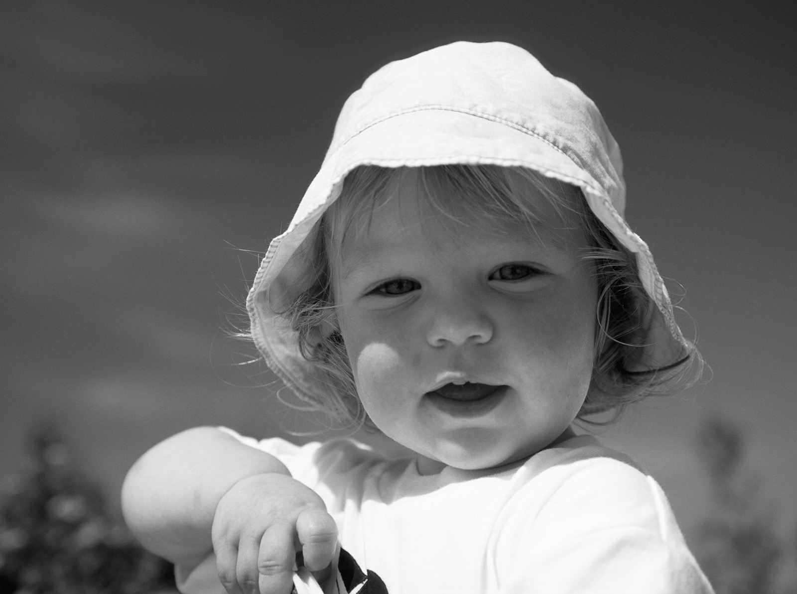 My wee girl Lauren aged about two years old holding a bucket and spade with chubby arms and a floppy hat on to protect her from...
