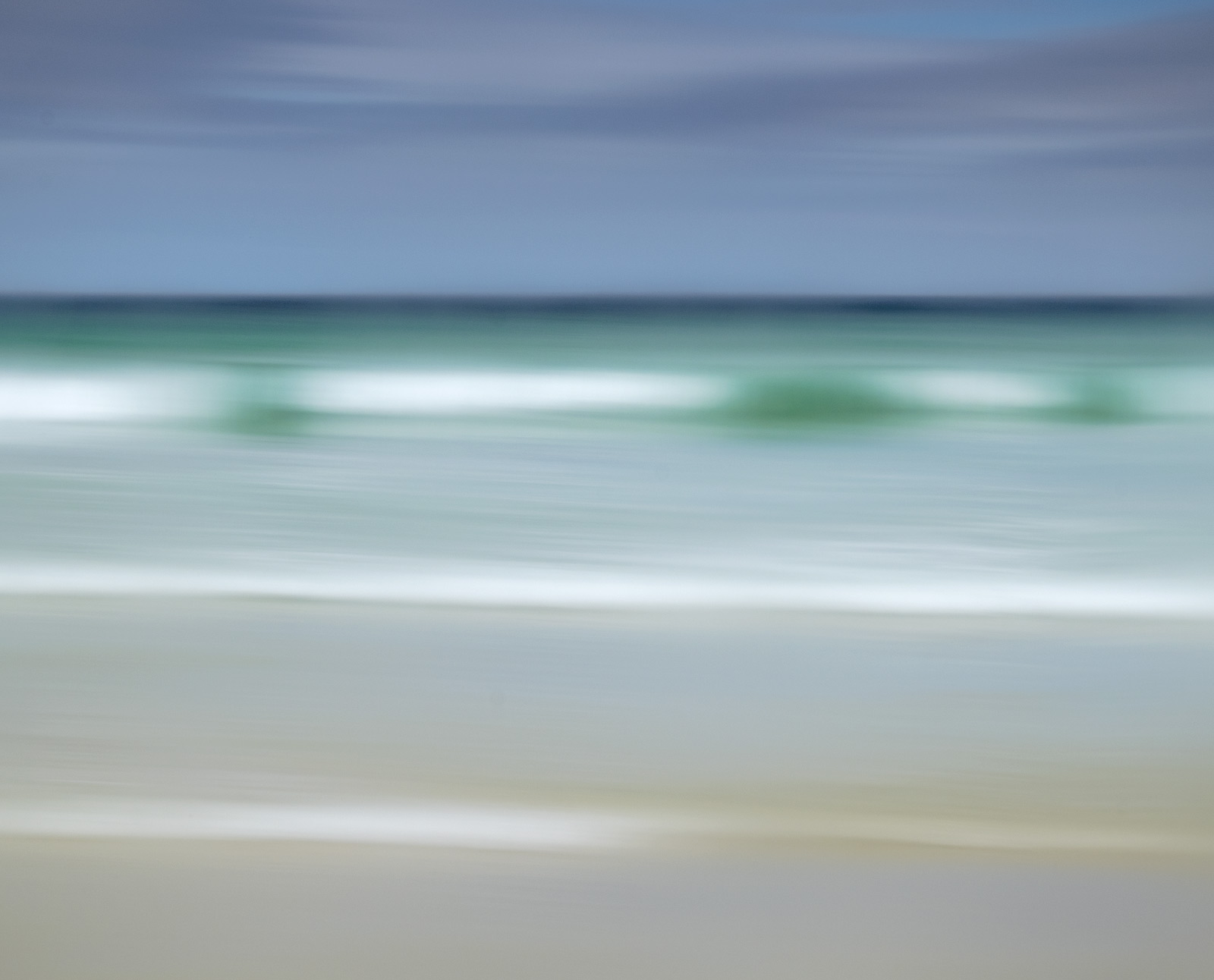A beautiful summer day with wave after breaking wave marching in from a turquoise sea rolling over a pale sand beach beneath...