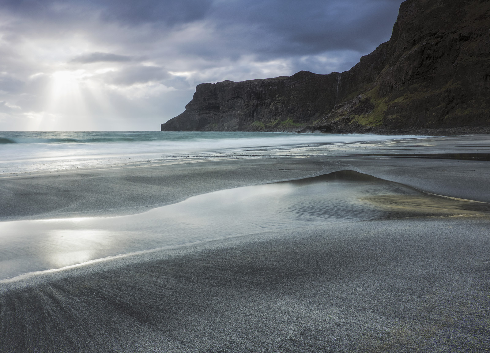 Talisker bay at sunset gazing across the unblemished marbled sands towards the black cliffs and the wispy waterfall that mistily...