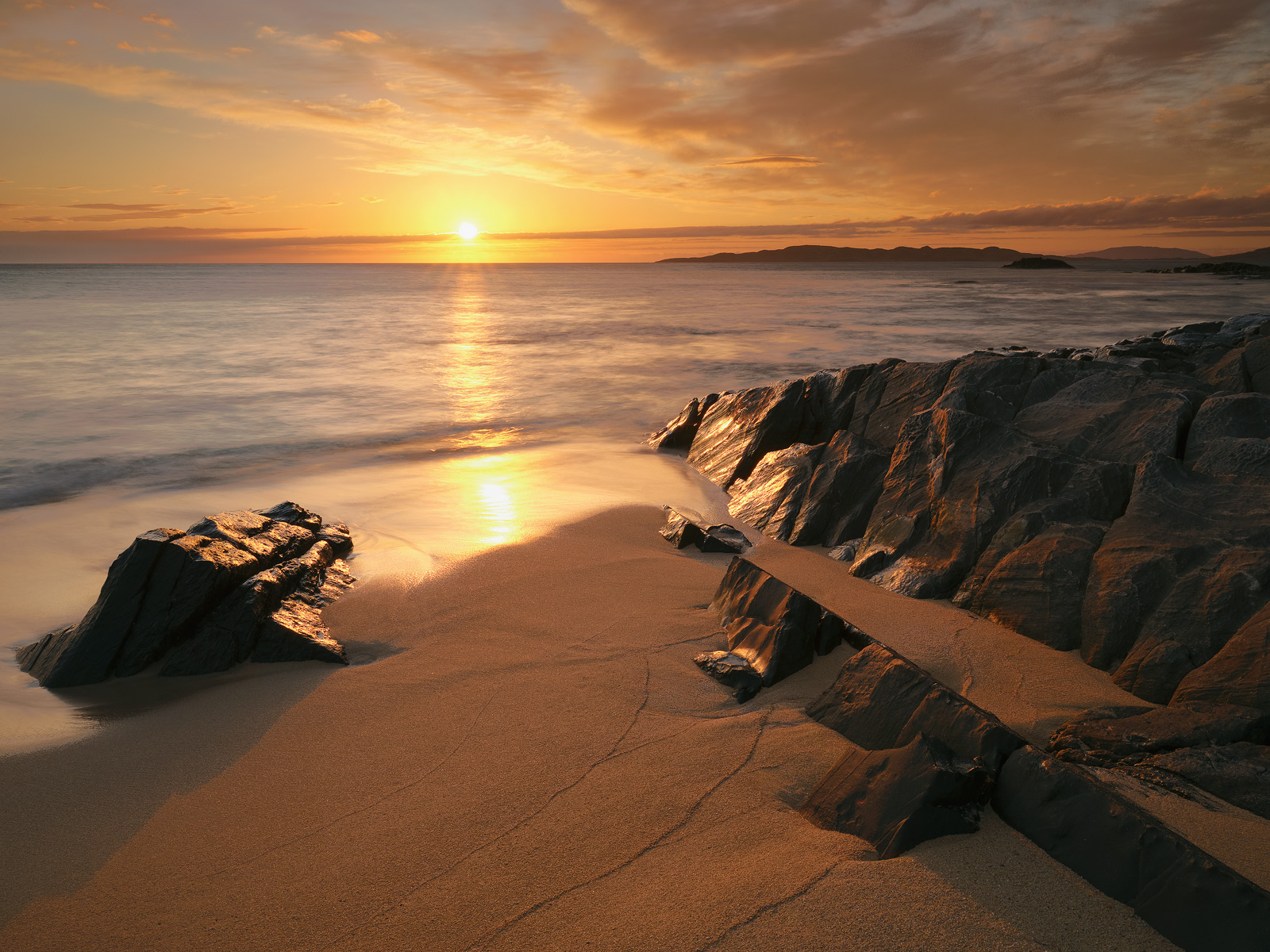 The tangerine ball of the setting sun glints off wet embedded rock and ignites the orange sand beach at Traigh Mhor on Harris.