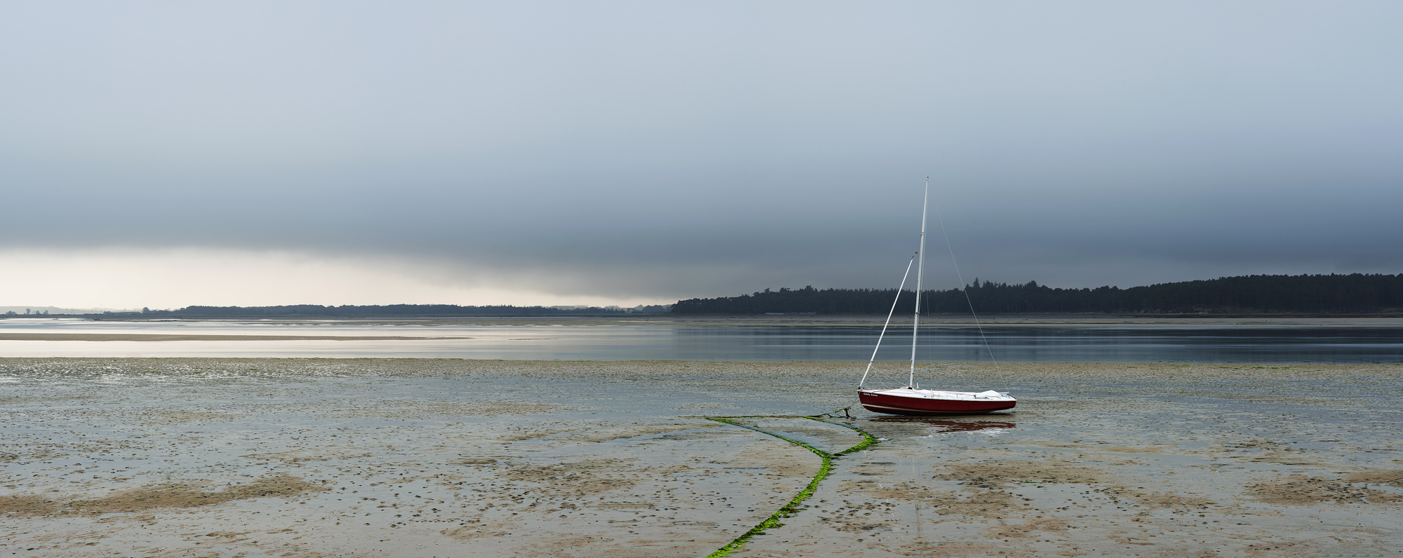 The Gandy Goose dinghy tethered on the foreshore as a storm beyond builds ominously over Forres across the Findhorn estuary.