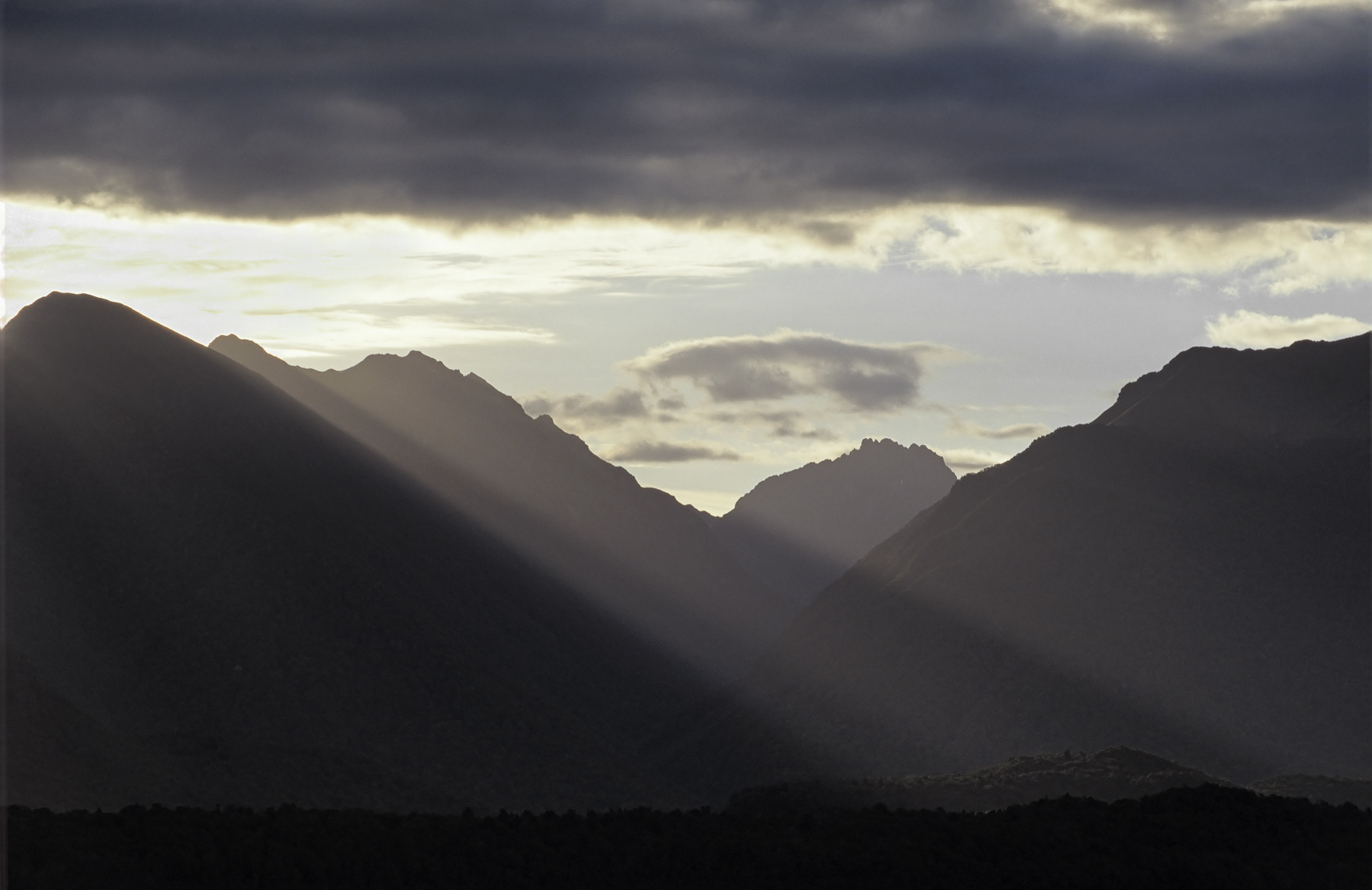 Brilliant sunshine erupts from behind a rolling base of heavy grey cloud over the mountains beyond Lake Manapouri and ladders...
