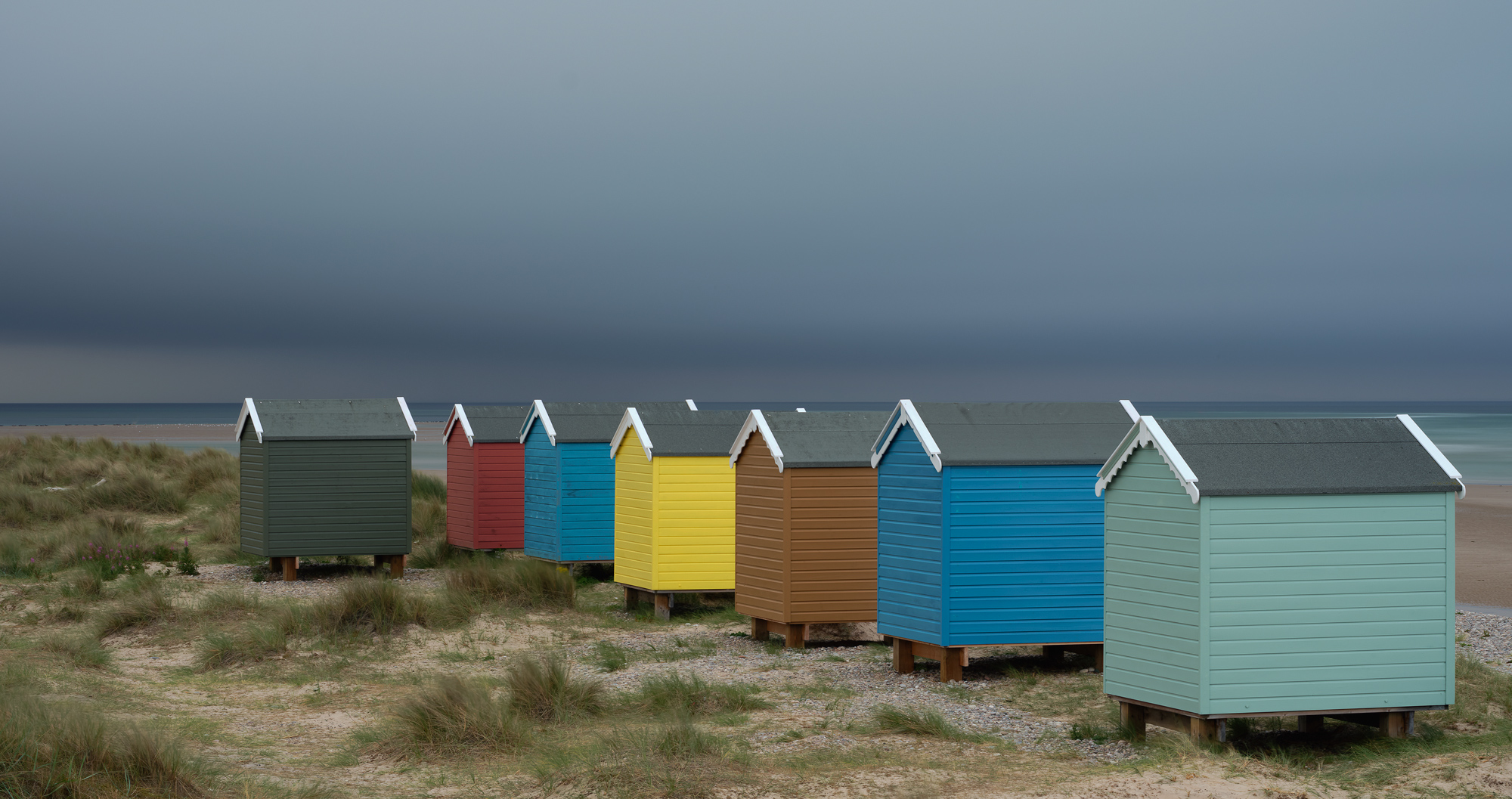 Cheerful beach huts in rainbow painted colours offer a bizarre juxtaposition to the forthcoming deluge about to hit Findhorn Bay.