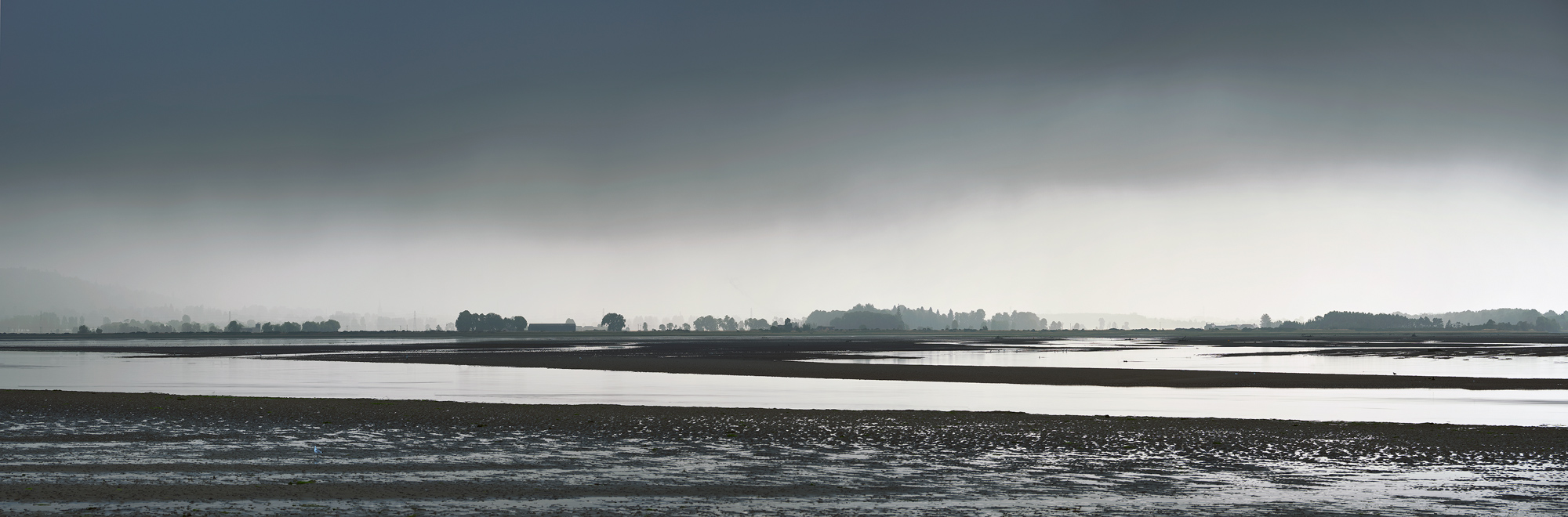 A thunderstorm broods on the horizon over Forres across the sand flats of the Findhorn estuary.