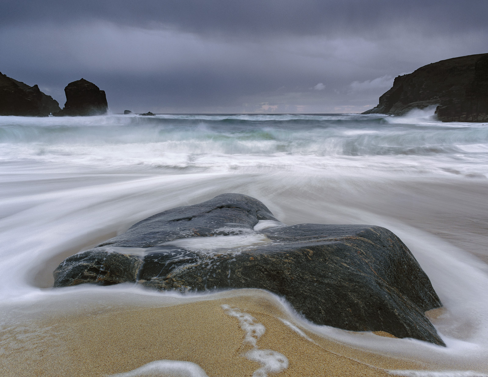 As the tide reached it's maximum height on Dail Beag beach it started to envelop the larger embedded gneiss half submerged in...