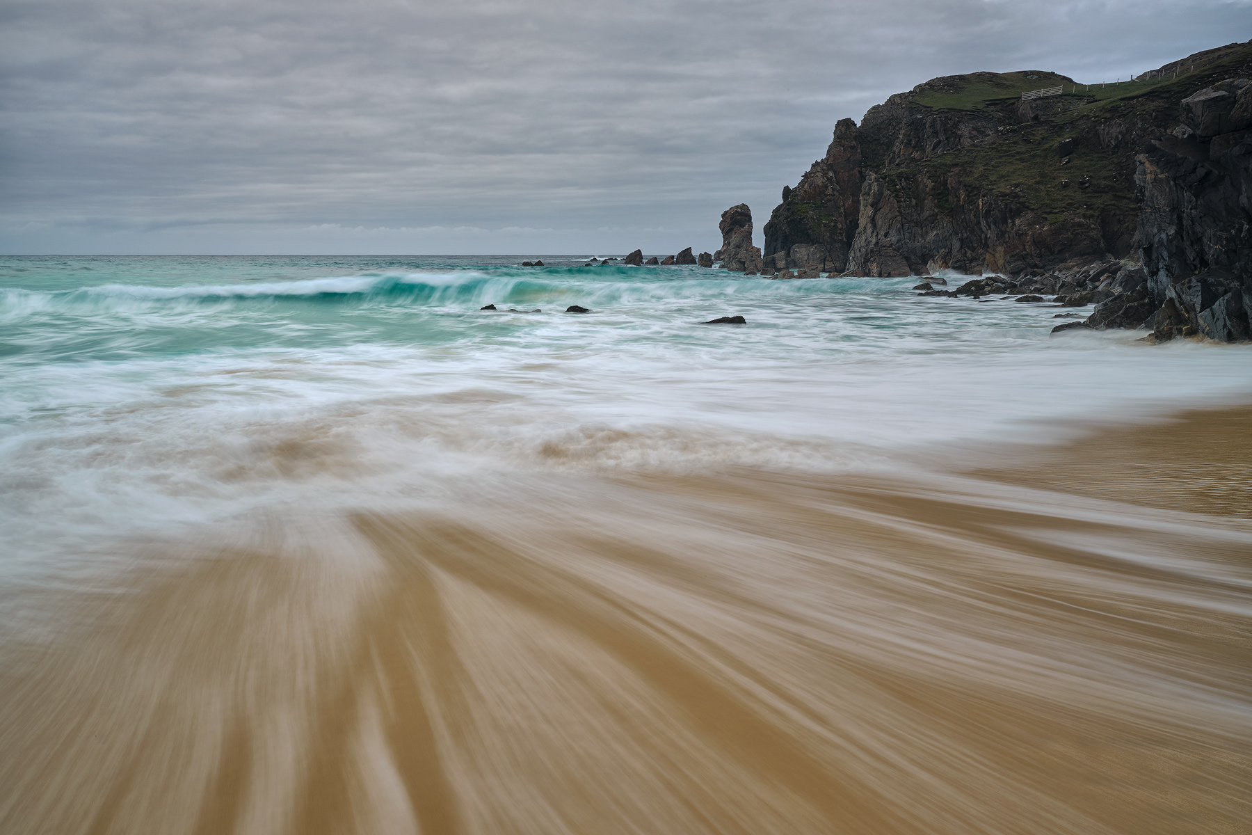 On the other side of Dail Mhor's golden beach on the west coast of Lewis are the sea stacks pummeled by a rough sea.