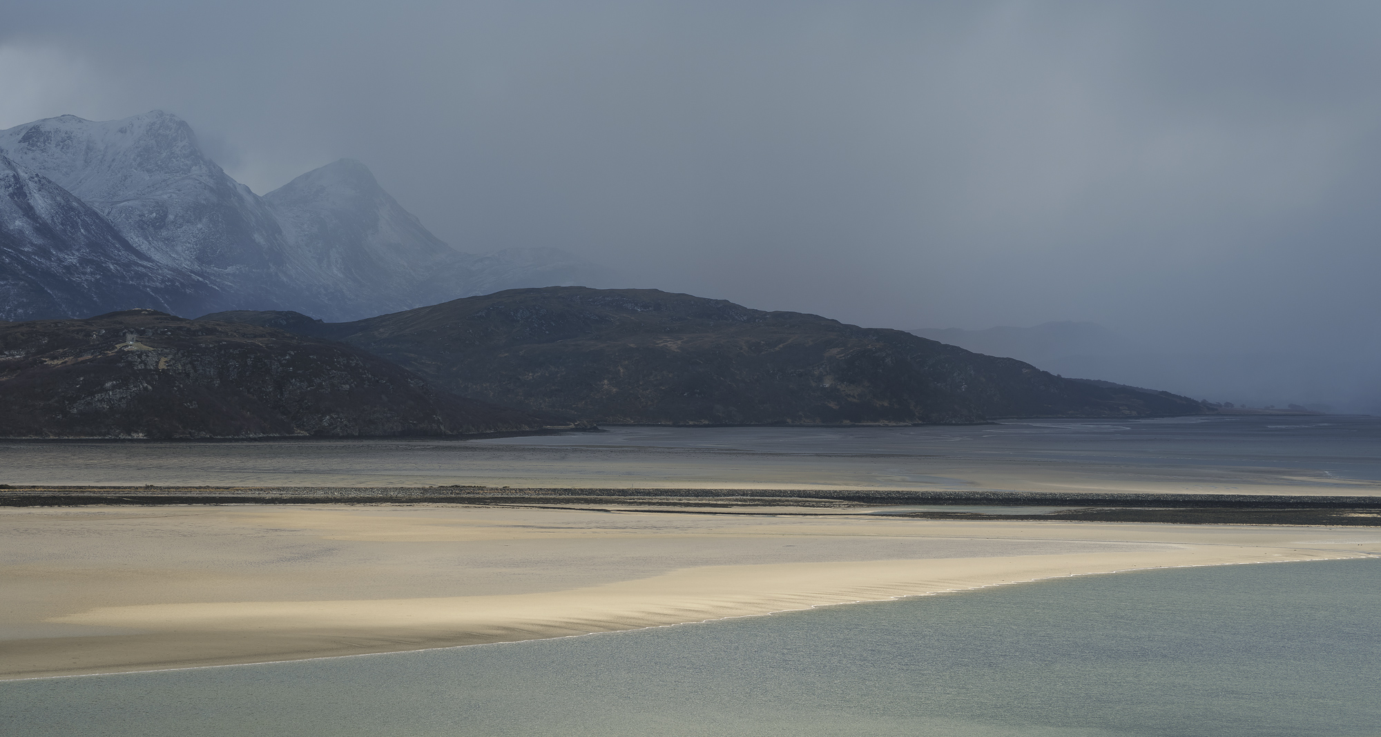 A spring squall complete with snow and hail obiterates the peaks of snow dusted Ben Loyal whilst traces of sunlight paint the estuary.