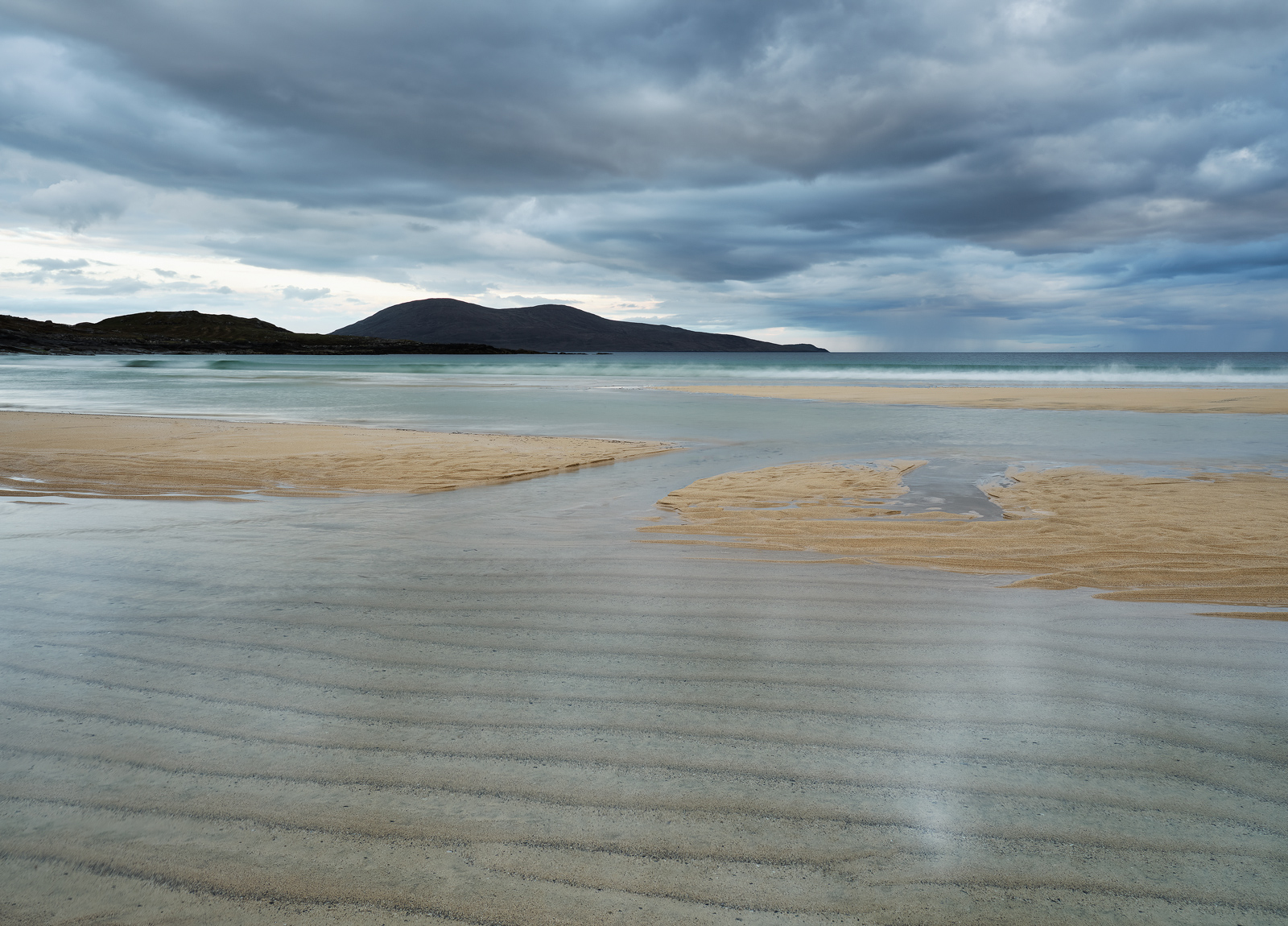Parallel tram lines form on Traigh Lar beach at low tide and traverse the entire beach creating strong patterns in the sand against a steely grey sky.