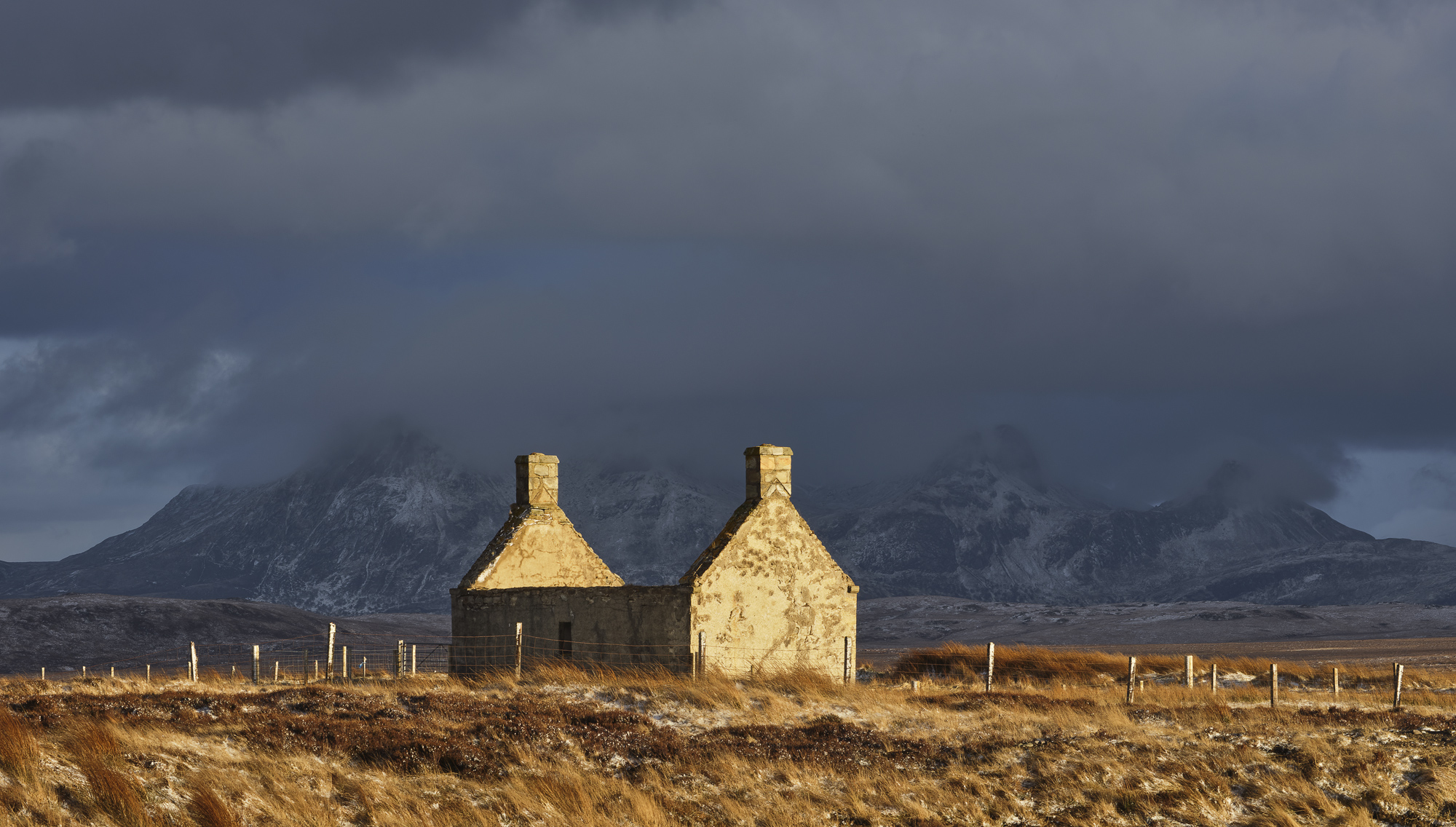 Gold painted Moine House with moody snow dusted Ben Loyal being consumed by black clouds.