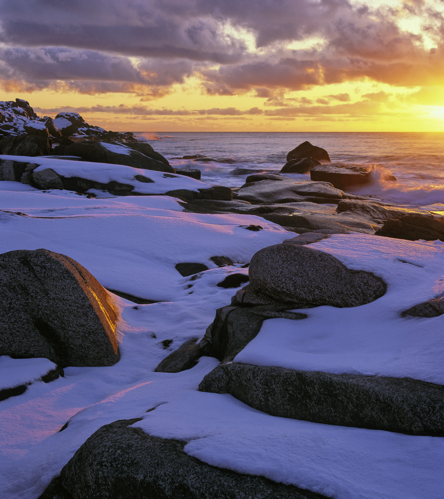 The setting sun scythes its way beneath bubbling cloud on snow covered uttakliev beach in the Lofoten Islands creating an interesting...