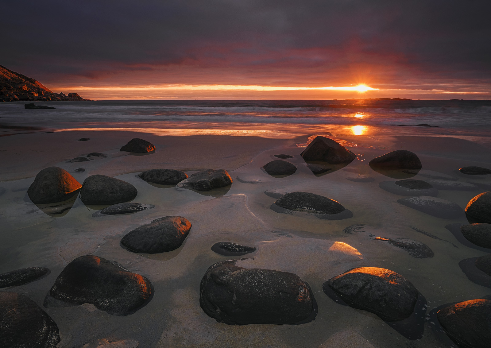 For a very short while as the setting sun passed through a ribbon of clearer sky the sun set scarlet across the black boulders...
