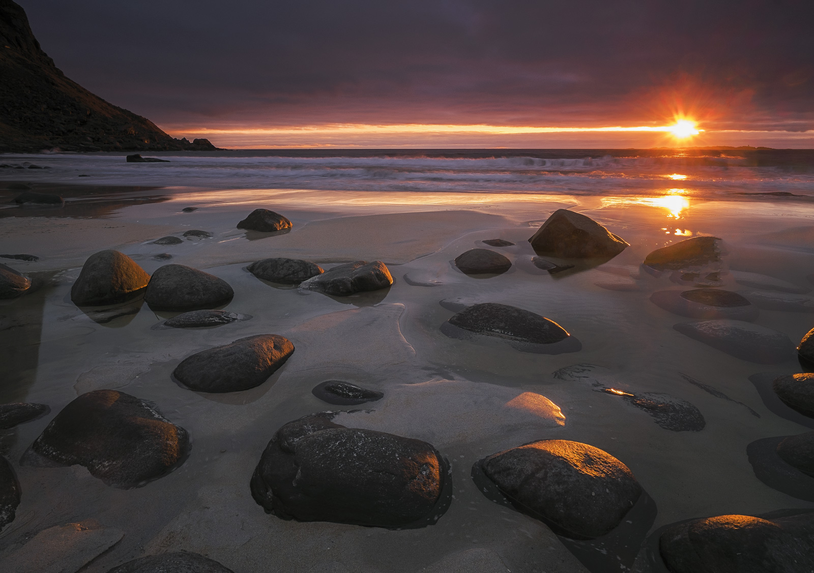 The sun sets in a blaze of powerful and blinding orange light illuminating the wet black rocks and turning them into nuggets...