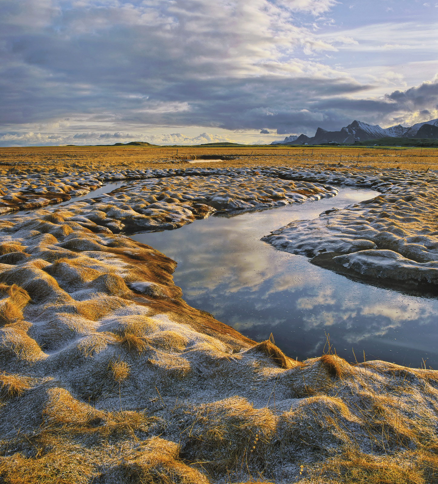 Behind Fredvang beach at Vollen are the grass plains that are criss-crossed by tidal channels that drain water into the sea.&...