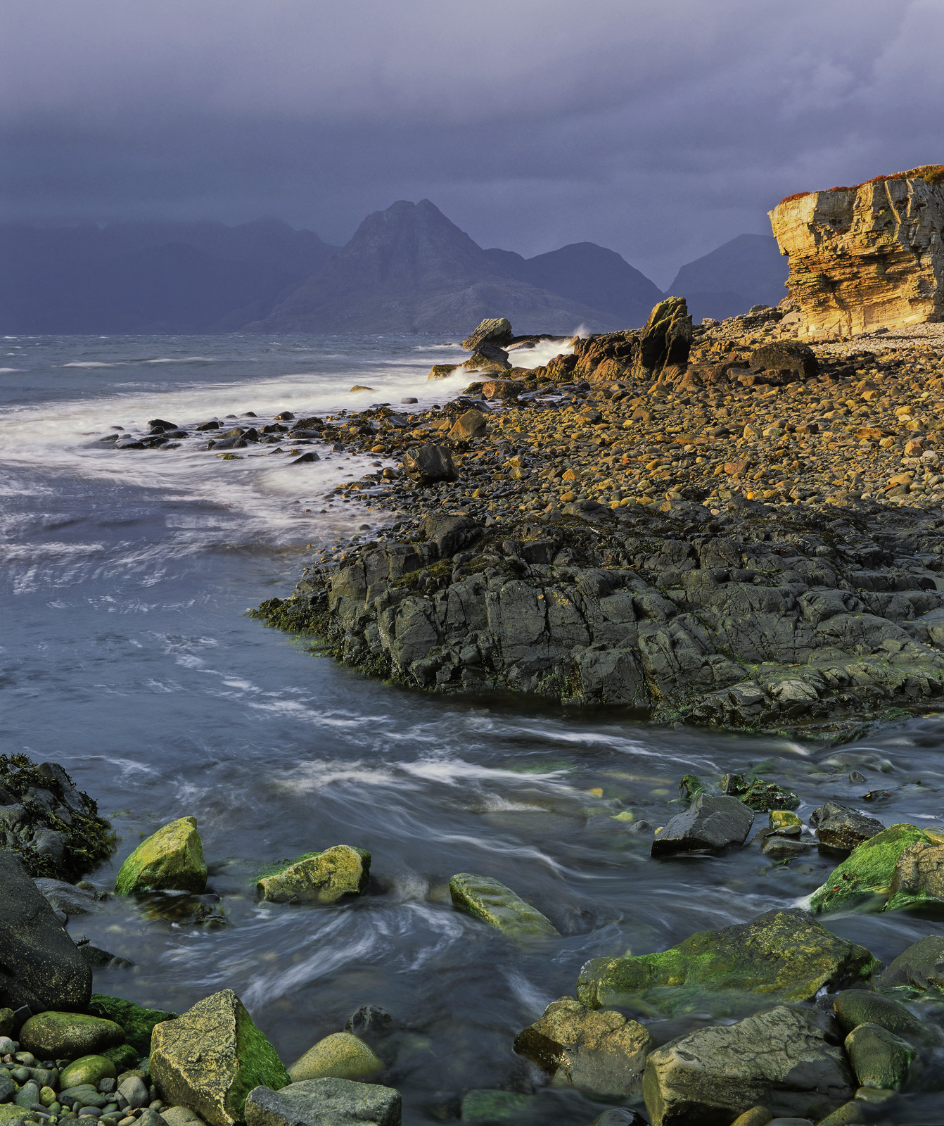 The black Cuillins glower beneath a dark and moody sky and all looks temporarily sombre and dark. Elgol very much suits...