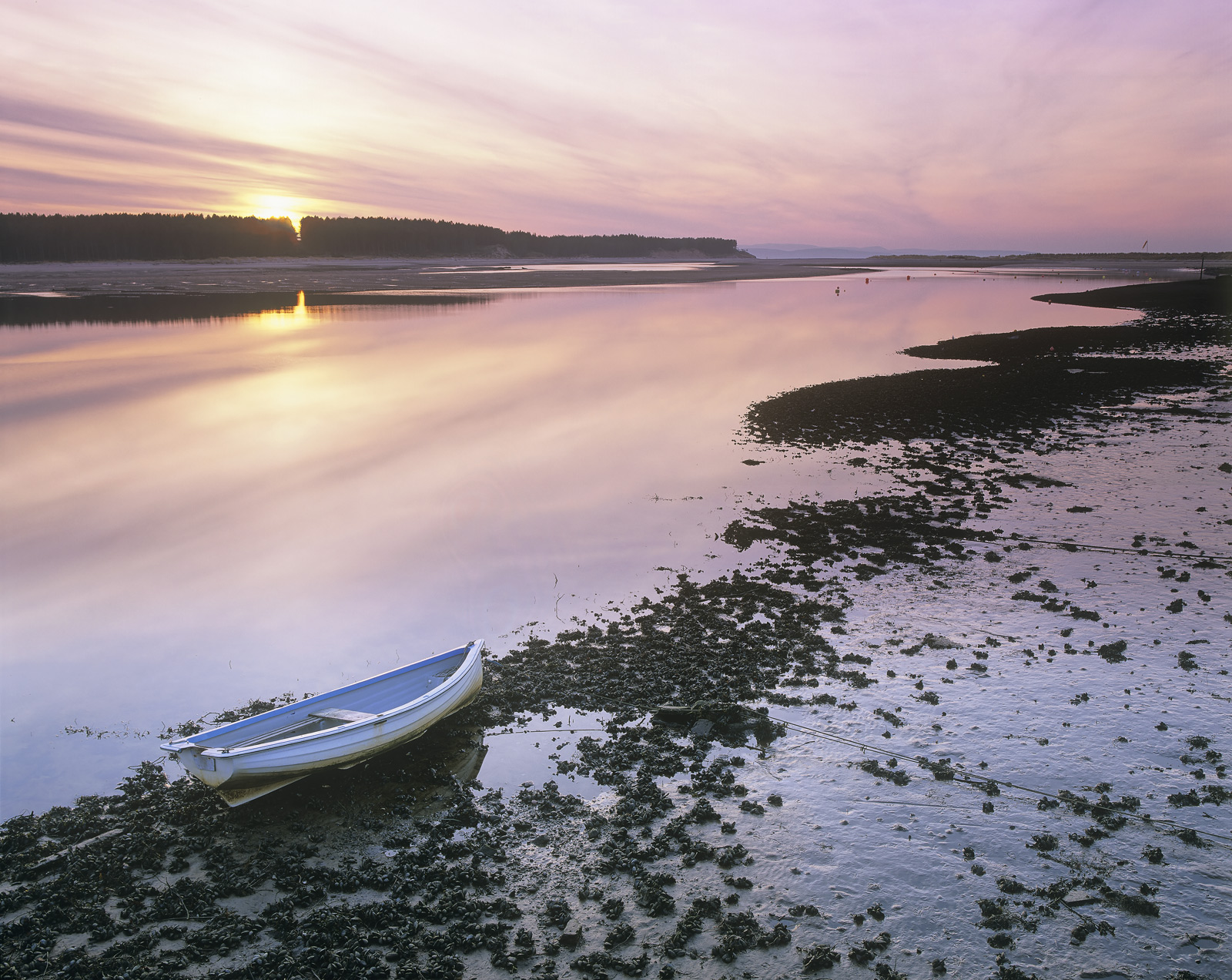 A beautiful soft misty pink summer sky hung over the Findhorn estuary at sunset whilst below a powder blue painted boat was waiting...