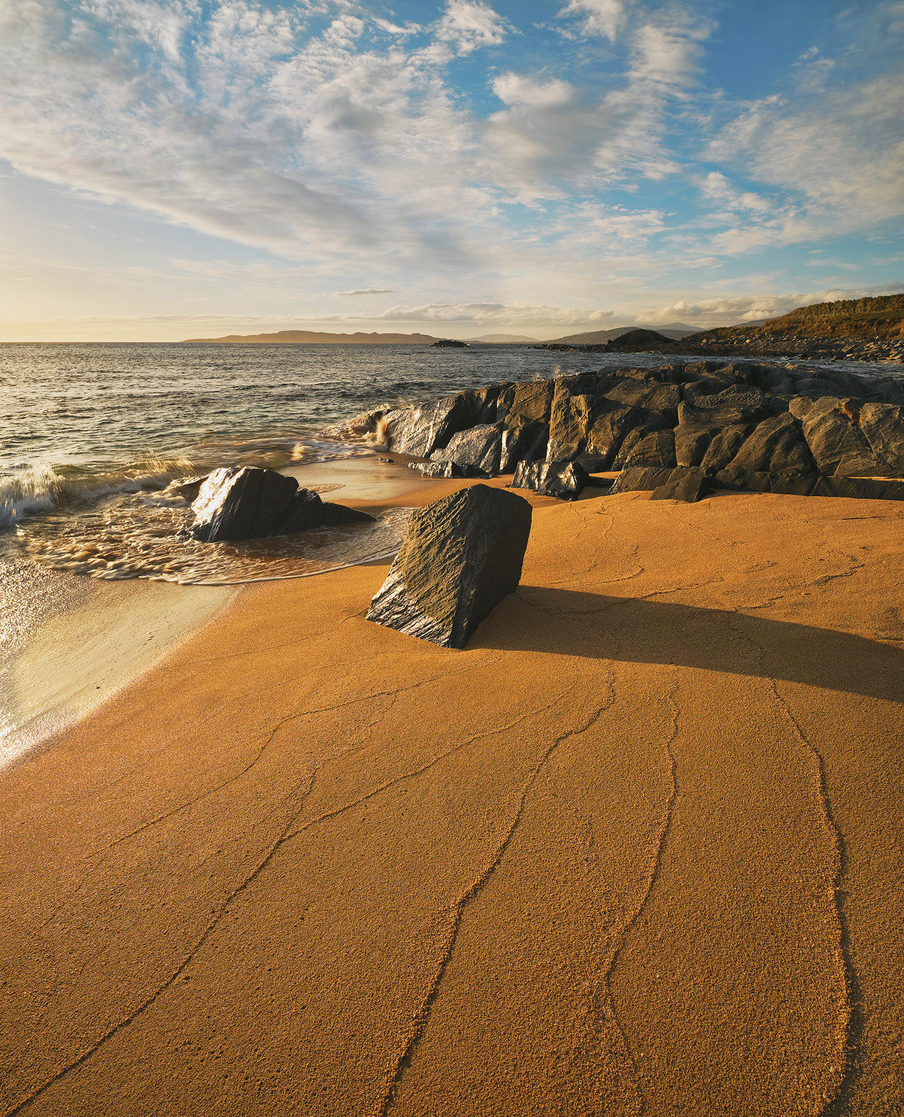 A spiders web of wave contours forms on Traigh Mhor's orange sand beach at sunset on the Isle of Harris.