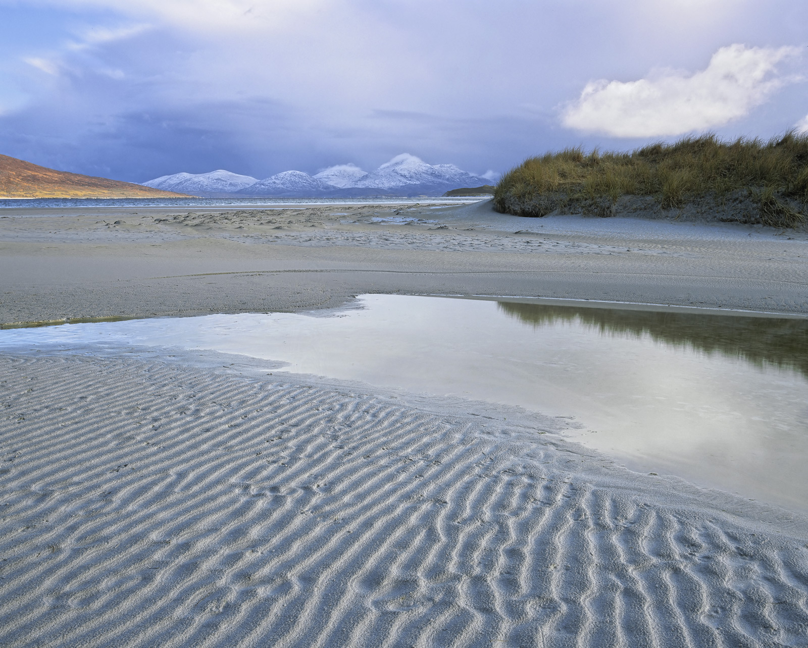 Where the river drains into the sea at Luskentyre bay it passes by the sand dunes of Seilebost beach rippling the sand and creating...