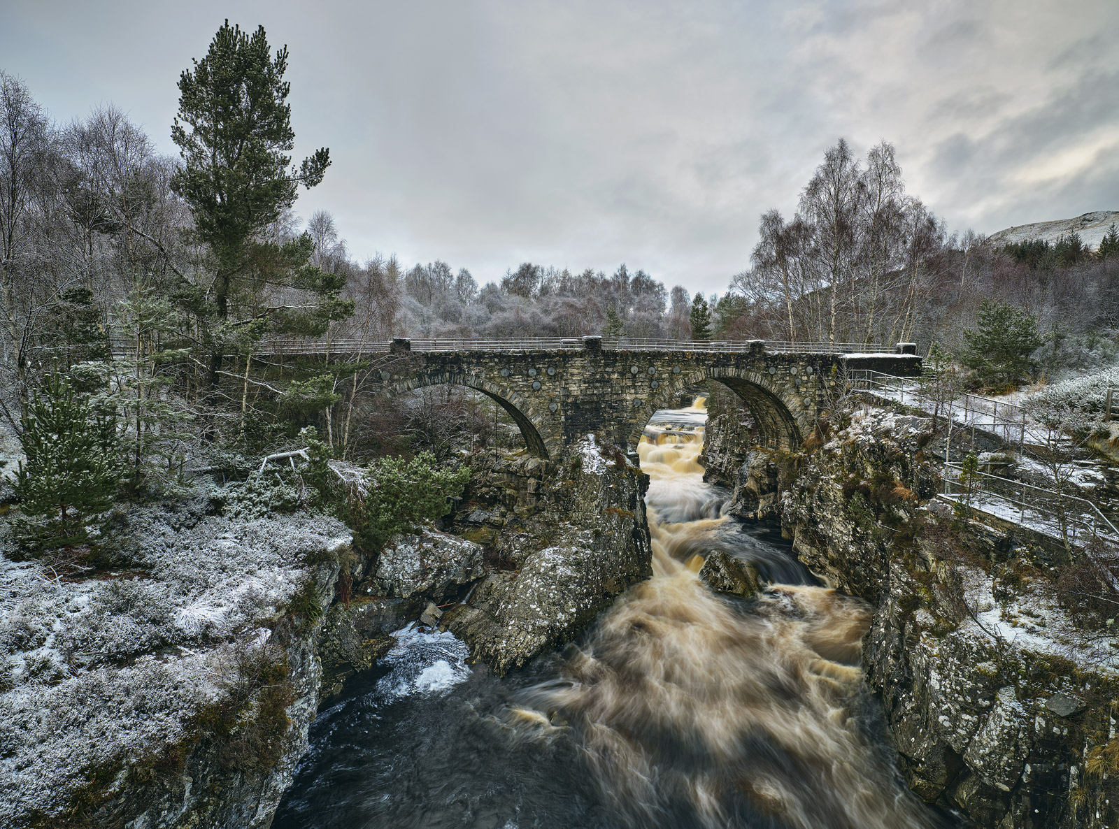 After a fresh snow fall the double arched old footbridge that crosses the river Garve is transformed and a torrent of peat stained...