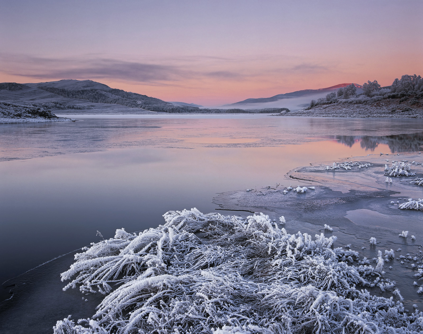 A sunrise across partially frozen Loch Achanalt looking toward Achnasheen and the pinkening of earth shadow with an accompanying...